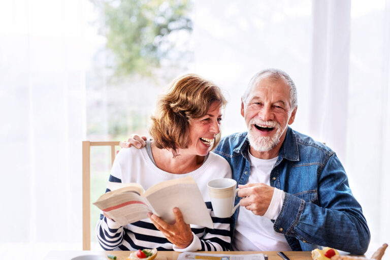 Vantage Pointe Village | Senior couple reading at table