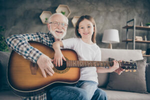 Vantage Pointe Village   Senior and his granddaughter sitting on couch with an acoustic guitar